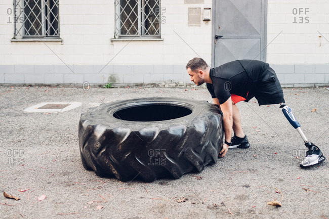 Man with prosthetic leg weight training with giant tire