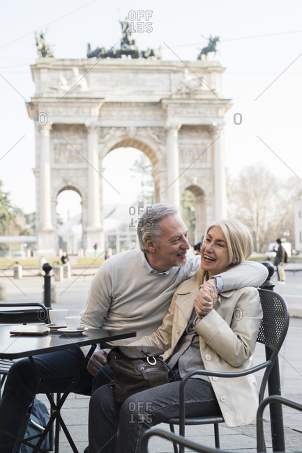 Senior couple laughing at cafe, Arch of Peace in background, Milan, Lombardia, Italy