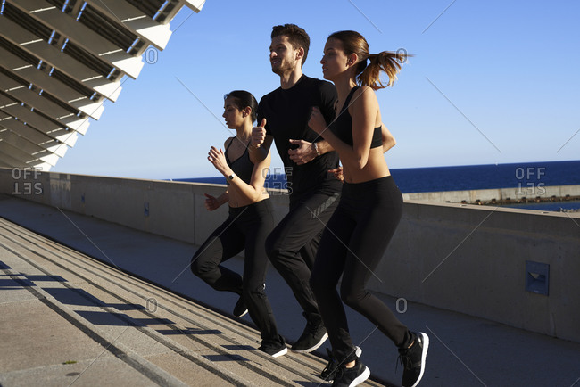 Friends jogging up steps in sports stadium