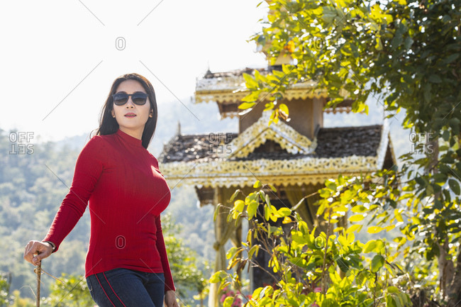Woman posing in front of shrine, Pai, Mae Hong Son, Thailand