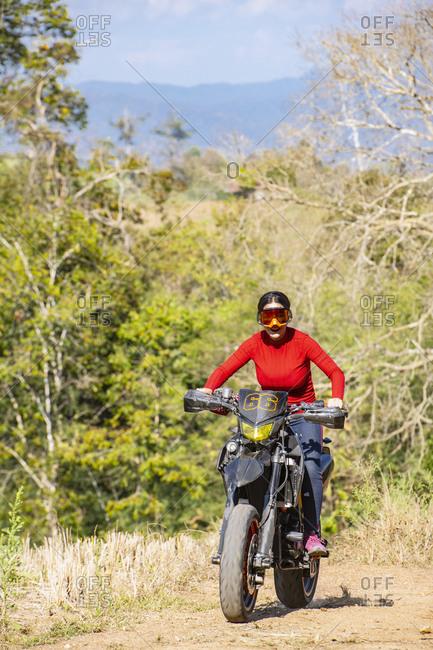 Biker riding motorbike on dirt track, Pai, Mae Hong Son, Thailand