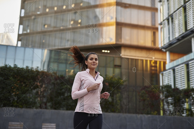 Woman jogging on sidewalk, Barcelona, Catalonia, Spain