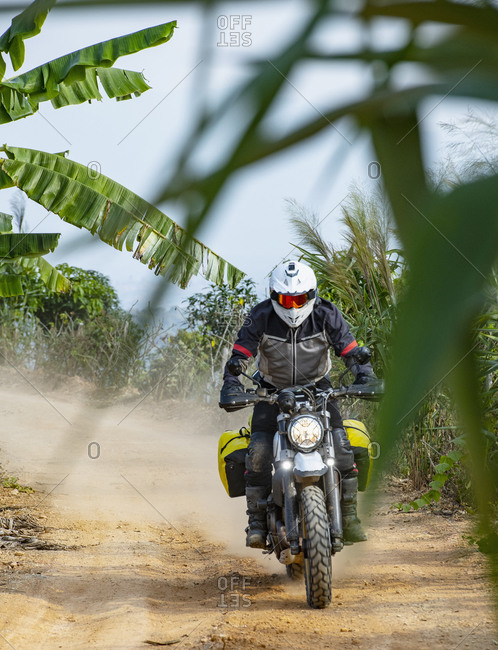 Biker riding scrambler type off road motorbike through banana plantation, Nan, Thailand
