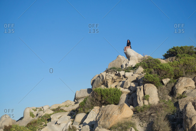Woman sitting on rock, Villasimius, Sardegna, Italy
