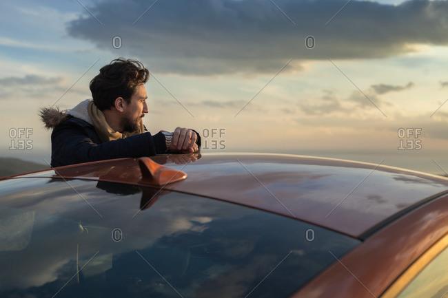 Man resting against car on roadside, enjoying view on hilltop