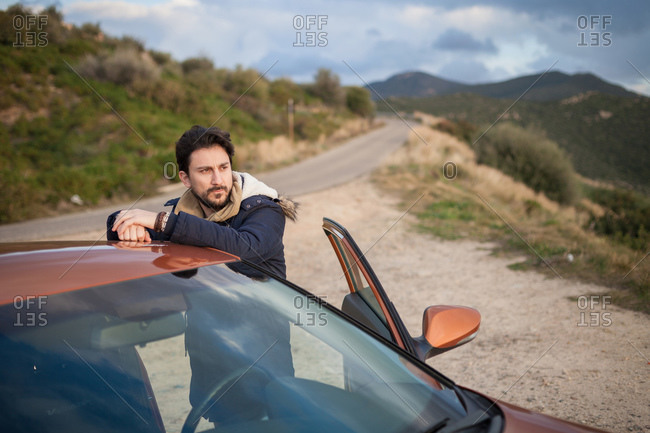 Man resting against car on roadside, enjoying view on hilltop, Villasimius, Sardegna, Italy