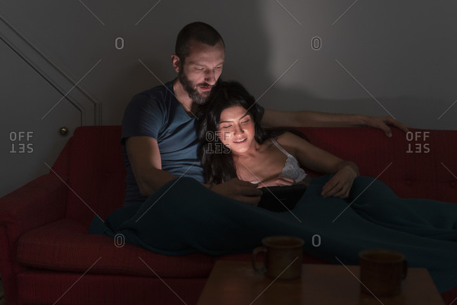 Hipster couple using digital tablet on sofa