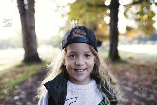 Little boy with long blond curly hair wearing a backwards baseball cap