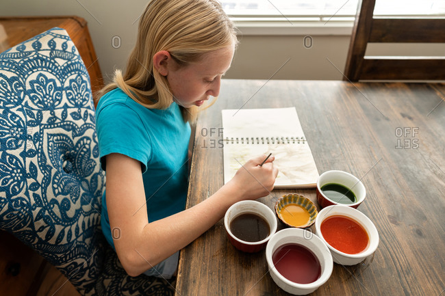 Young blonde girl painting with watercolors
