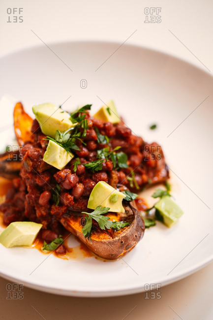 Beans and avocado on top of sweet potato