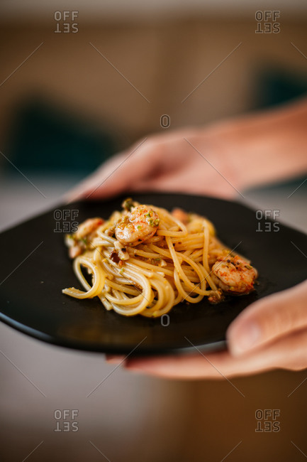 Woman holding a black plate with pasta and shrimp