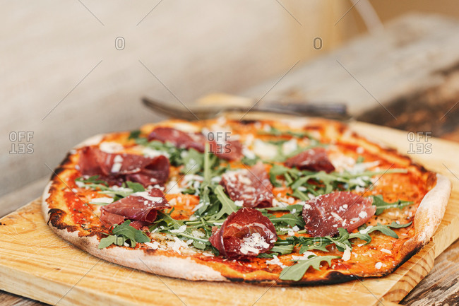 Woodfired pizza with arugula and prosciutto