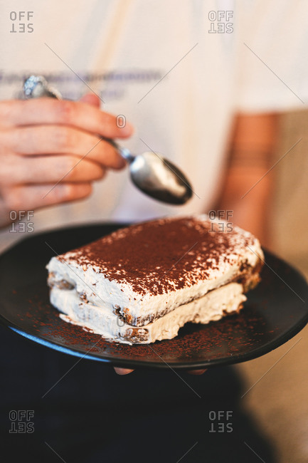 Person eating a piece of tiramisu with spoon