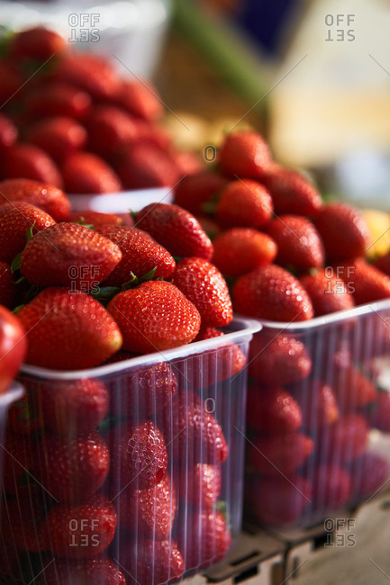 Red juicy strawberries in containers at a grocery store