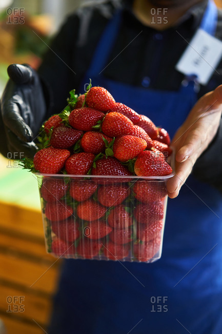 Worker holding container filled with red juicy strawberries at a grocery store