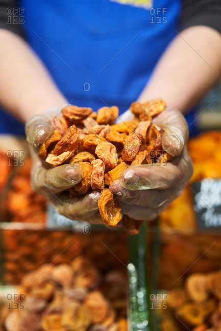 Worker holding dried apricots in hands at a grocery store