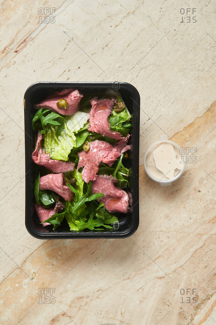 Salad with beef in black container on marble surface