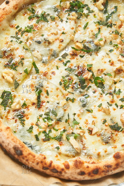 Close up of a cheesy pizza with chopped nuts
