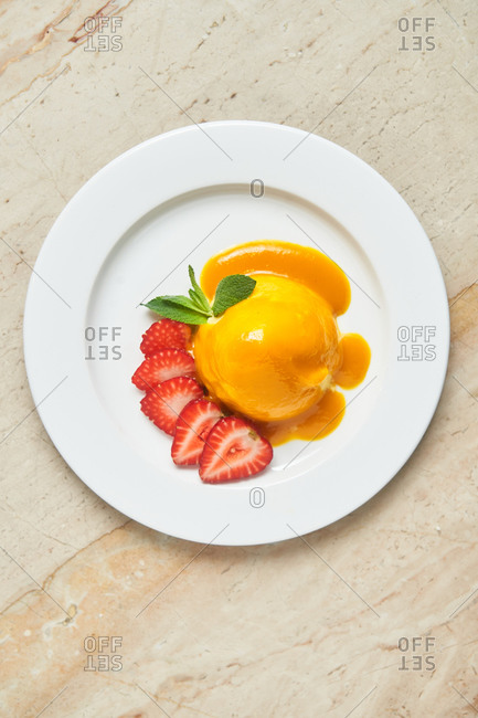 Peach dessert with strawberries on light marble surface