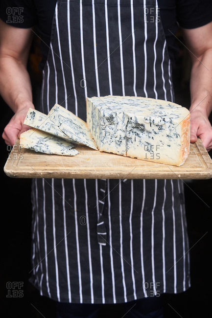 Person holding fresh block of blue cheese