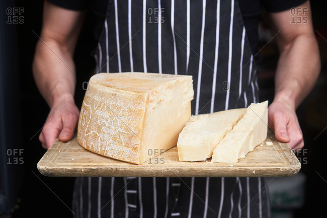 Person holding fresh block of parmesan cheese