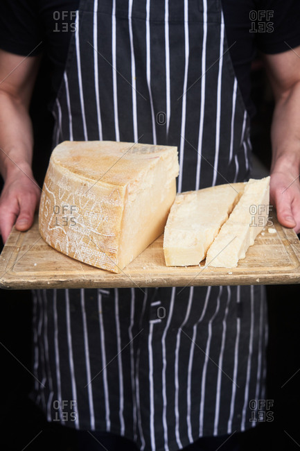 Chef holding fresh block of parmesan cheese