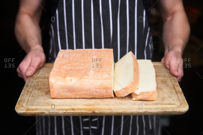 Chef holding fresh block of muenster cheese