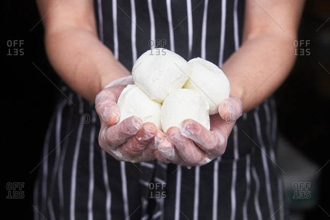 Chef holding balls of mozzarella cheese