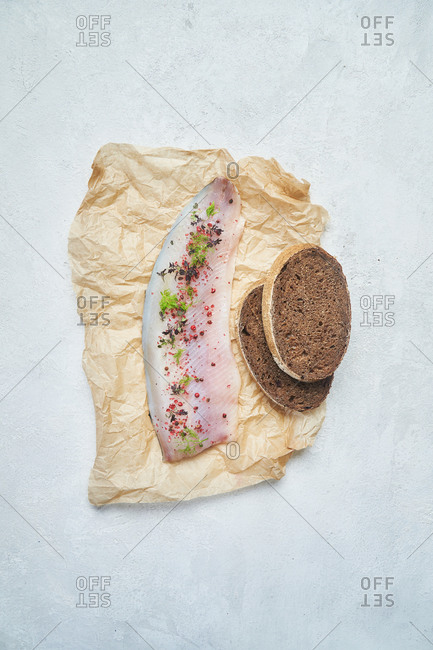 A raw fish fillet seasoned on parchment paper and bread