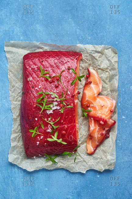 A raw salmon fillet seasoned on parchment paper