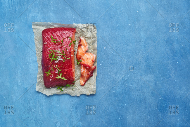 A raw salmon fillet seasoned on parchment paper with blue background