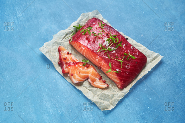Raw salmon fillet seasoned on parchment paper with blue background