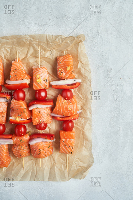 Overhead view of raw salmon kabobs on parchment paper
