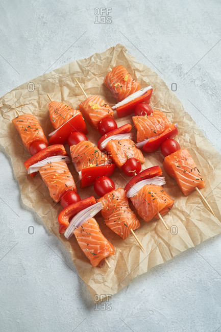 Top view of raw salmon kabobs on parchment paper