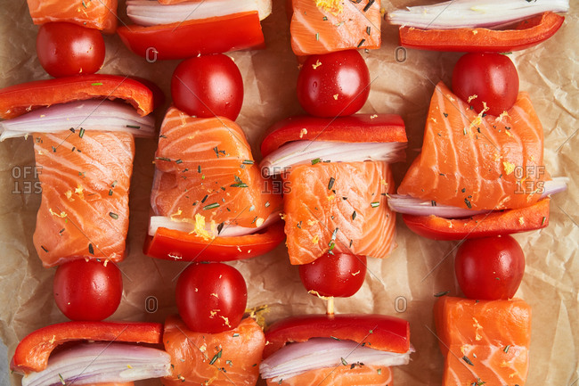 Detail of raw salmon kabobs on parchment paper