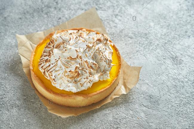 Lemon meringue tart on gray background