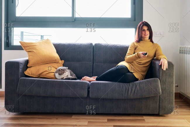 Woman on her couch using remote and watching tv with her exotic cat during corona virus outbreak