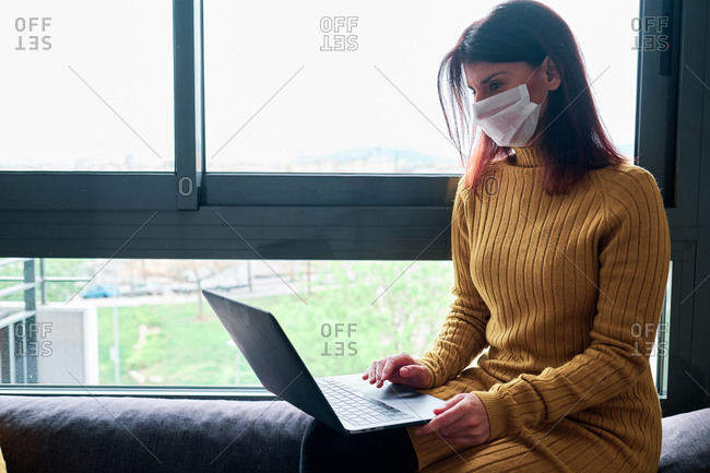 Woman working with laptop at home with mask on her couch on a cloudy day during coronavirus outbreak