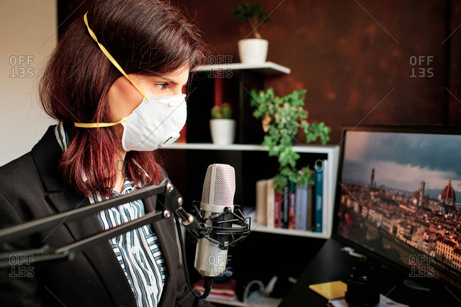 Woman with mask working at home and podcasting with a microphone