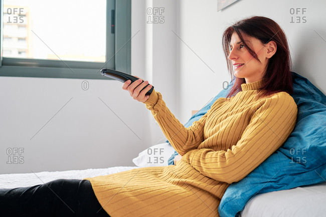 Woman on her bed using the remote during corona virus outbreak