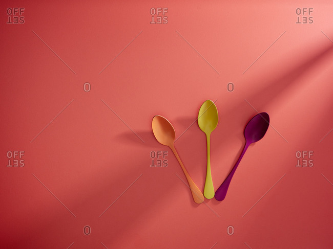 Top view of bunch of vivid multicolored spoons arranged on side of red background