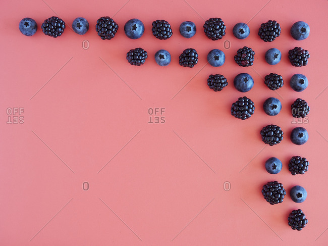 Creative natural background with fresh ripe blueberries and blackberries arranged in corner of pink surface