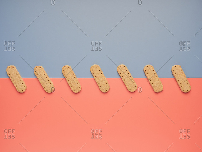 Top view of yummy crunchy cookies arranged in line like patches between gray and coral backgrounds