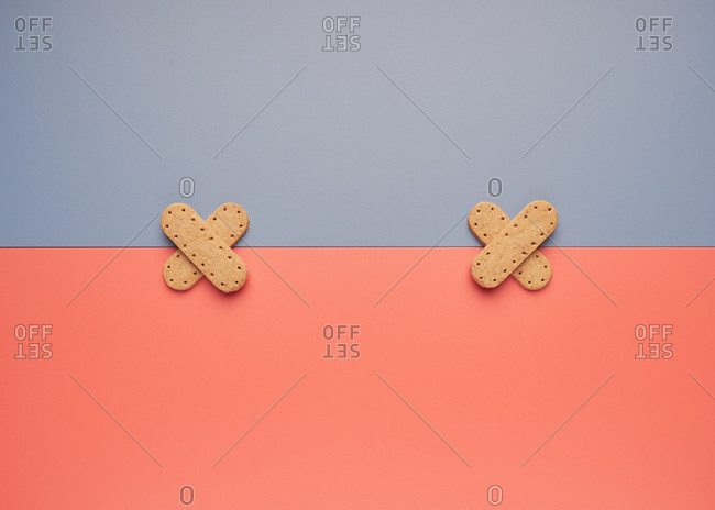 Top view of delicious crispy cookies arranged in shape of crossed patch on line between gray and coral backgrounds