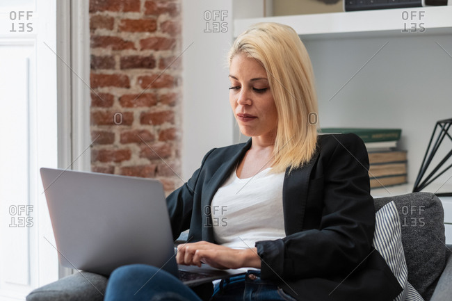 Cheerful blonde businesswoman smiling and browsing laptop while sitting in comfortable armchair near fireplace in cozy room working remotely from home