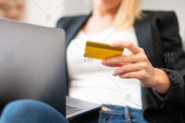 Cropped unrecognizable blonde female in casual clothes entering credit card credentials on laptop while sitting in comfortable armchair and making online purchases at home