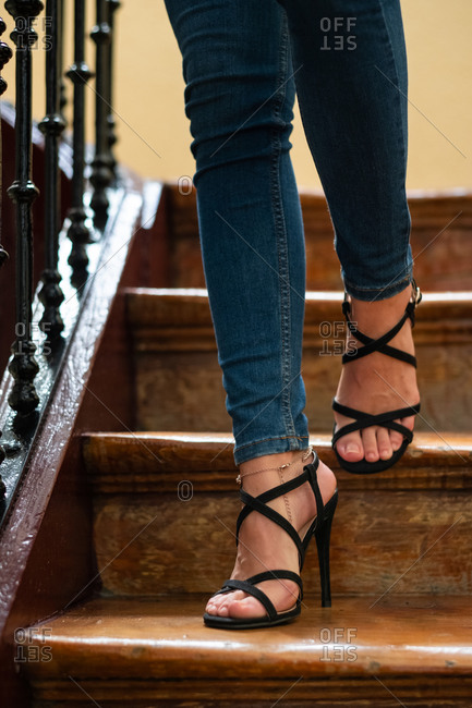 Unrecognizable female in jeans and high heeled sandals walking down lumber stairs at home