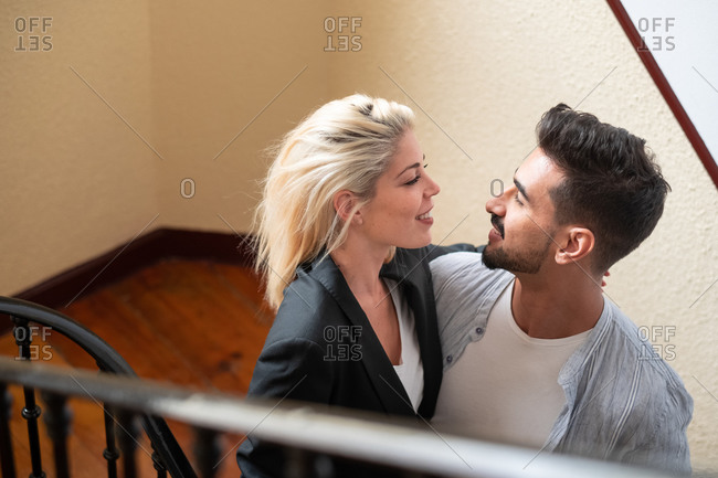 From above diverse man and woman smiling looking at each other and embracing each other while standing on stairway at home