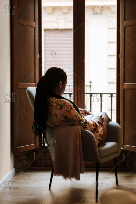 Ethnic woman with book resting at home