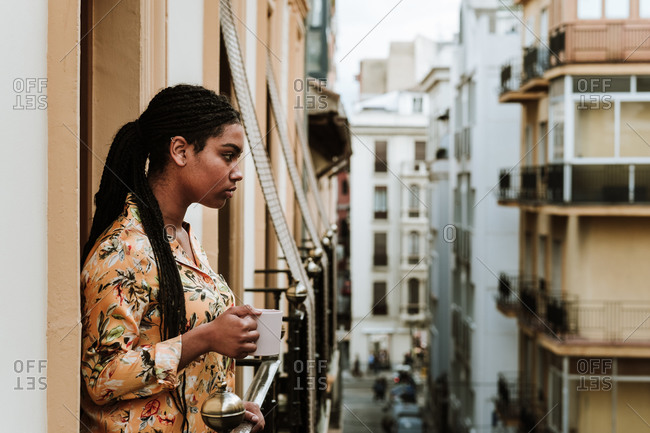 Side view of tranquil young African American female in casual clothes with cup of hot drink standing on balcony of old residential house in city